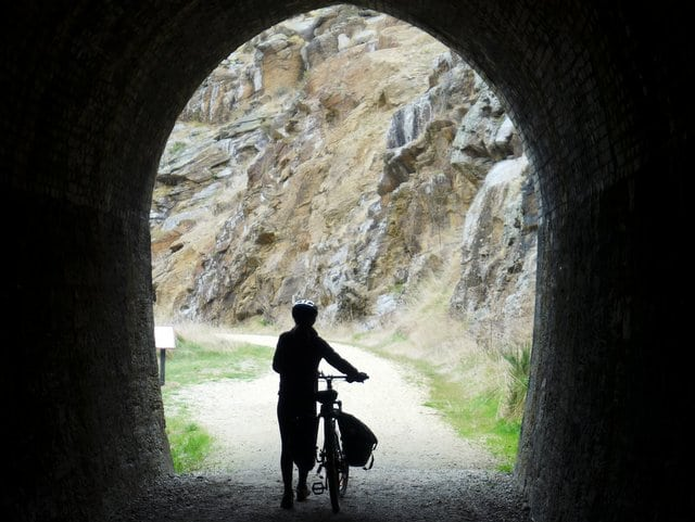 Pushing a bike out of a tunnel on the Otago Cenral Rail Trail